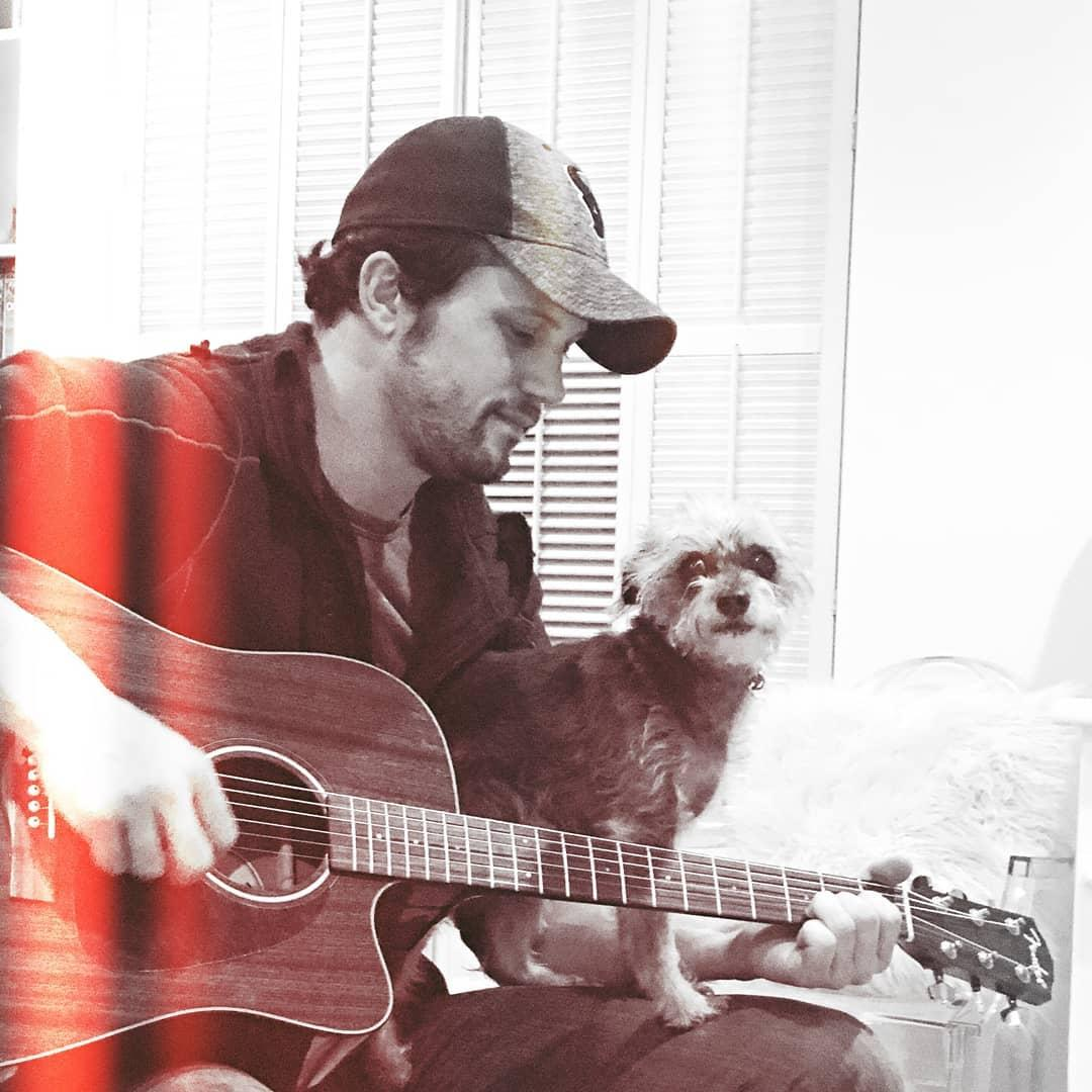 Nathan Parsons with his dog making music
